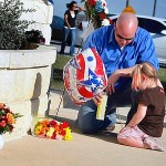 KILLEEN, TX - NOVEMBER 07:  U.S. Army Specialist Ryan Hill and his daughter, Emma Hill,3, pray together as they light a candle and lay flowers at the front gate to Fort Hood following a shooting rampage on the grounds November 7, 2009 in Killeen, Texas. U.S. Army Major Nidal Malik Hasan, an army psychiatrist, killed 13 people and wounded as many as 30 in a shooting rampage at the Soldier Readiness Center on the grounds of the military base Fort Hood on November 5, 2009.  (Photo by Joe