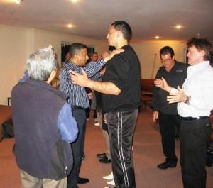Pastor Daniel praying for a huge guy