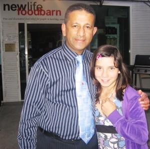 Pastor Daniel with girl who was the first baby saved through Options Plus Care 10 years ago